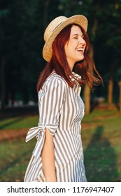 laughing young attractive woman wearing striped dress and straw hat