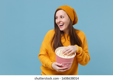 Laughing young brunette woman girl in sweater and hat posing isolated on blue background. People emotions in cinema lifestyle concept. Mock up copy space. Watching movie film hold bucket of popcorn