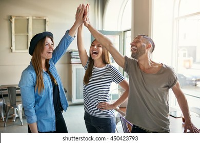 Laughing young business entrepreneurs in informal trendy clothing standing celebrating a success giving a high fives gesture