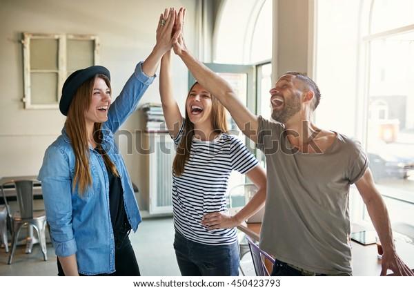 Junge Unternehmer in informeller, trendiger Kleidung lachen, die einen Erfolg feiern und eine tolle Fünf-Sterne-Geste vermitteln