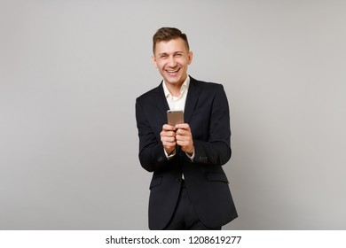 Laughing young business man in classic black suit, shirt using mobile phone, typing sms message isolated on grey background in studio. Achievement career wealth business concept. Mock up copy space