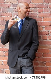 Laughing young business man with a glass of white wine, near a brick wall.