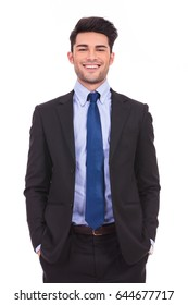laughing young businessman standing with hands in pockets on white background