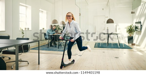 Laughing young businesswoman riding a scooter around a large modern office during her work break
