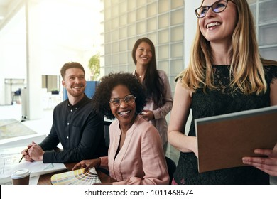 Laughing young businesswoman standing in a modern office with a diverse group of work colleagues smiling in the background