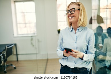 Laughing young businesswoman wearing glasses and leaning against a glass wall in an office reading messages on her cellphone