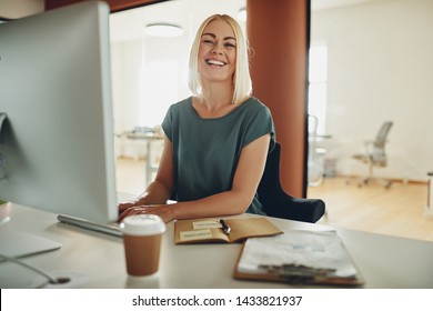 Laughing young businesswoman working on a computer while sitting at her desk in a large modern office