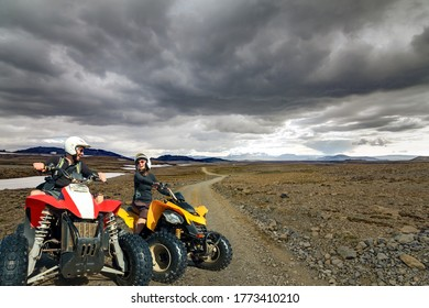 Laughing young couple ATV quad bikers smile joyful, cheerful and driving in icelandic Highland Landscape with quadbikes on dirt road F550 in Kaldidalur, Iceland.