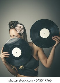 Laughing young fashionable woman with face behing two vinyl LP records, studio background