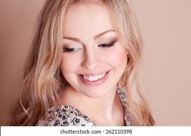 Laughing young girl 20-22 year old over beige. Looking away. Long blonde hair. Closeup portrait. Emotions.