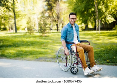 Laughing young handicapped man in a wheelchair