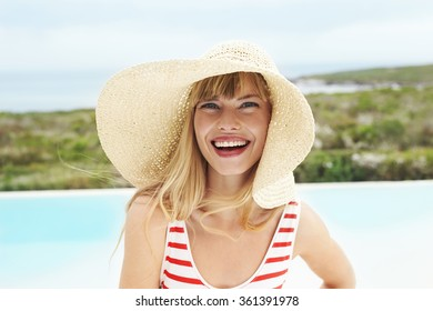 Laughing young lady in sunhat and swimsuit, portrait