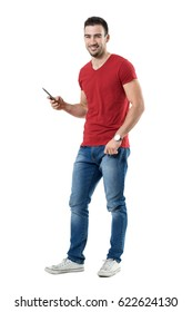 Laughing young man holding mobile phone reading humorous message. Full body length portrait isolated over white studio background.