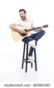 Laughing young man playing guitar while sitting on stool  isolated on white
