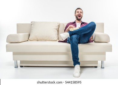 Laughing young man sitting on couch with popcorn isolated on white