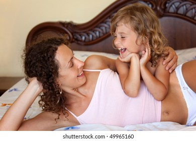 laughing young mother and daughter lying and embracing on bed in hotel room.