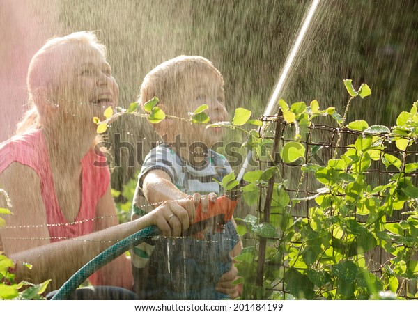 Laughing young mother and her small son playing with a jet of water from a sprinkler nozzle allowing the spray to fall back over themselves in a summer garden