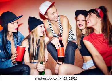 Laughing young people sitting on couch at private party, as they talk and drink beer having fun late at night