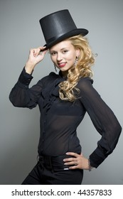 Laughing young pretty girl in black with top hat in studio