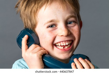 laughing young red hair boy with sparkling blue eyes, freckles and a tooth missing holding an old fashioned telephone giggling and talking, grey background studio