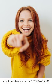 Laughing young redhead woman pointing at the camera with a vivacious smile and focus to her face