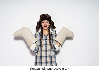 laughing young Russian girl in a warm hat with ear-flaps holds winter boots