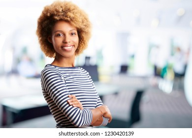 A laughing young sales assistant business woman standing with arms crossed at the office.