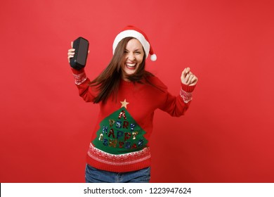 Laughing young Santa girl dancing and jumping, holding portable wireless bluetooth music speaker isolated on red background. Happy New Year 2019 celebration holiday party concept. Mock up copy space