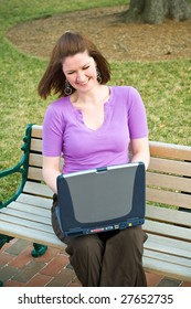 Laughing Young Student Girl Using Wireless Internet Laptop Technology and laughing on a park bench
