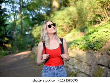 laughing young woman with backpack walking through the park