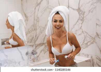 Laughing young woman in bra and towel around her head brushing her teeth while leaning on a sink at the bathroom