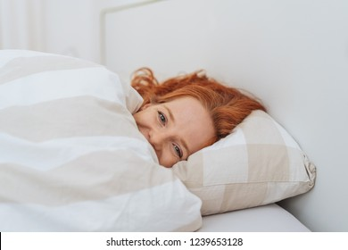 Laughing young woman cuddling under the duvet peeking out at the camera with mischievous eyes in a close up view