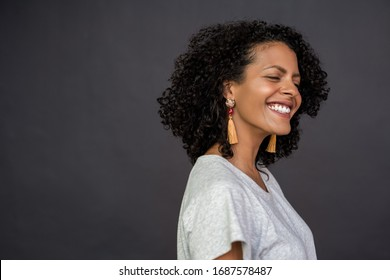 Laughing young woman with curly brown hair standing with her eyes closed in front of a gray background