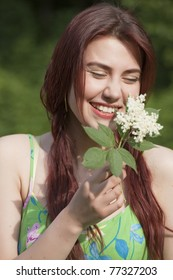 laughing young woman with flower in a park