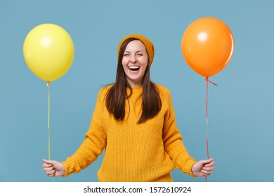 Laughing young woman girl in sweater hat posing isolated on blue background studio portrait. Birthday holiday party people emotions concept. Mock up copy space. Celebrating hold colorful air balloons
