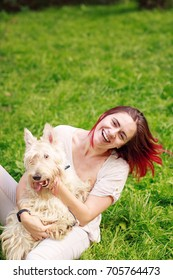 Laughing young woman having fun with dog outside