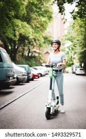 Laughing young woman with helmet on an electric scooter