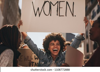 Laughing young woman holding a banner during a protest. Group of females activist protesting on road for women empowerment.