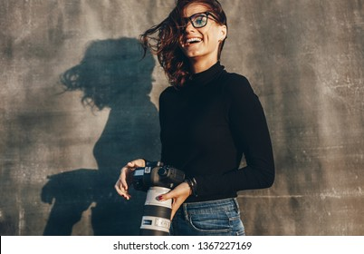 Laughing young woman holding a dslr camera against brown background. Successful female photographer on a photo shoot.