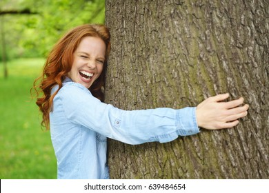 Laughing young woman hugging a large tree in a lush green spring park with her eyes closed in a conceptual image of loving nature