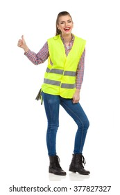 Laughing young woman in lime green reflective vest showing thumb up and looking at camera. Full length studio shot isolated on white.