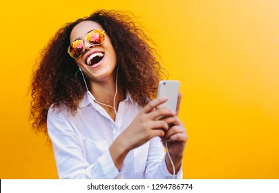 Laughing young woman listening to music on earphones using a cell phone. African girl with curly hair wearing sunglasses against yellow wall listening to songs on smart phone.