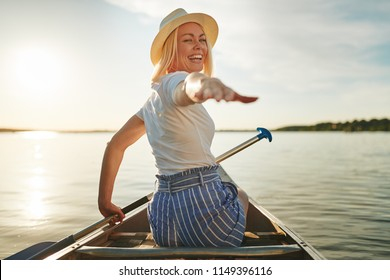 Laughing young woman looking back over her shoulder and reaching out with her hand while paddling a canoe on a lake in summer