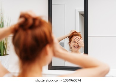 Laughing young woman looking at herself in a mirror as she covers one eye with her hand with focus to the reflection