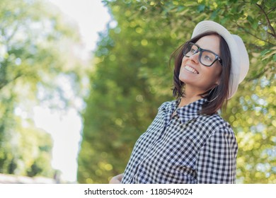 Laughing young woman looking to side or something in front of blurred nature background. Close-up female in forest