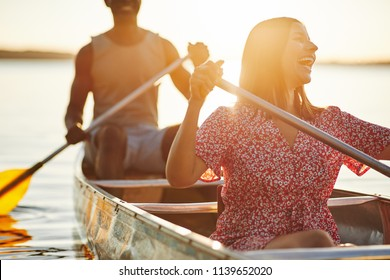 Laughing young woman paddling a canoe on a still lake with her boyfriend on a late afternoon in summer