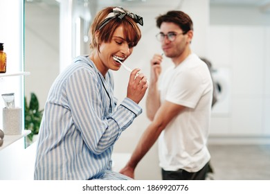 Laughing young woman in pajamas sitting on her bathroom sink and brushing her teeth with her boyfriend