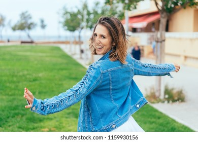 Laughing young woman running across a green urban field looking back at the camera with a happy smile
