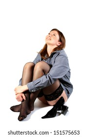 Laughing young woman in shirt and black stockings on a white background.