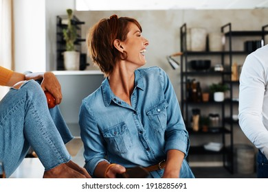 Laughing young woman standing at a counter in her kitchen and preparing food for a dinner party with her friends